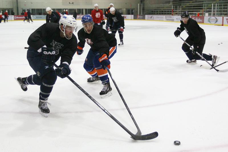 Winnipeg Jets Andrew Ladd, left, and New York Islanders Travis Hamonic, center,  battle for the puck during an informal hockey practice in Winnipeg, Manitoba, on Wednesday, Sept. 19, 2012. The league locked out its players at last weekend, its fourth shutdown since 1992. (AP Photo/The Canadian Press, John Woods)