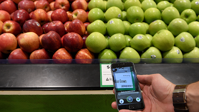 Green and red apples on a shelf in Woolworths as a man holds up a Scan&Go phone app.