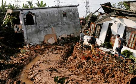 People walk past damaged houses during a rescue mission after a garbage dump collapsed and buried dozens of houses in Colombo