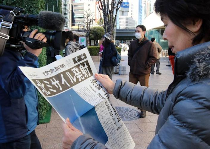 A woman reads an extra edition newspaper in Tokyo about North Korea's rocket launch (AFP Photo/Yoshikazu Tsuno)