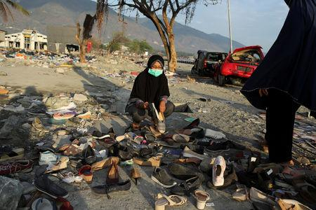 Women try to pair shoes found at a beach hit by the tsunami in Palu, Central Sulawesi, Indonesia, October 9, 2018. REUTERS/Jorge Silva