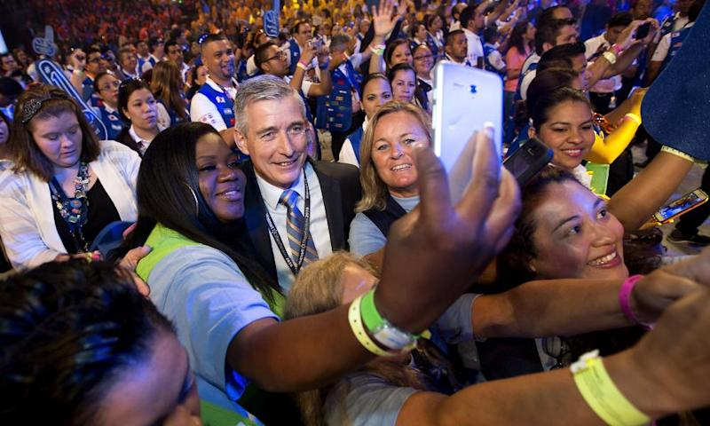Greg Foran (center), chief executive officer of Walmart, takes photos with associates before the annual Walmart shareholders meeting in 2016. The company has announced it has achieved its goal to buy $20bn worth of goods and services from women-owned businesses in the US over five years.