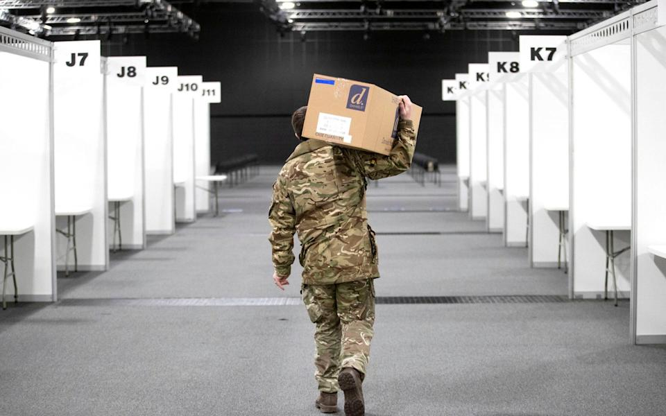 A member of the Royal Scots Dragoon Guard carries in supplies as part of the final preparations setting up a mass covid vaccination centre at the P and J Live Arena in Aberdeen - PA