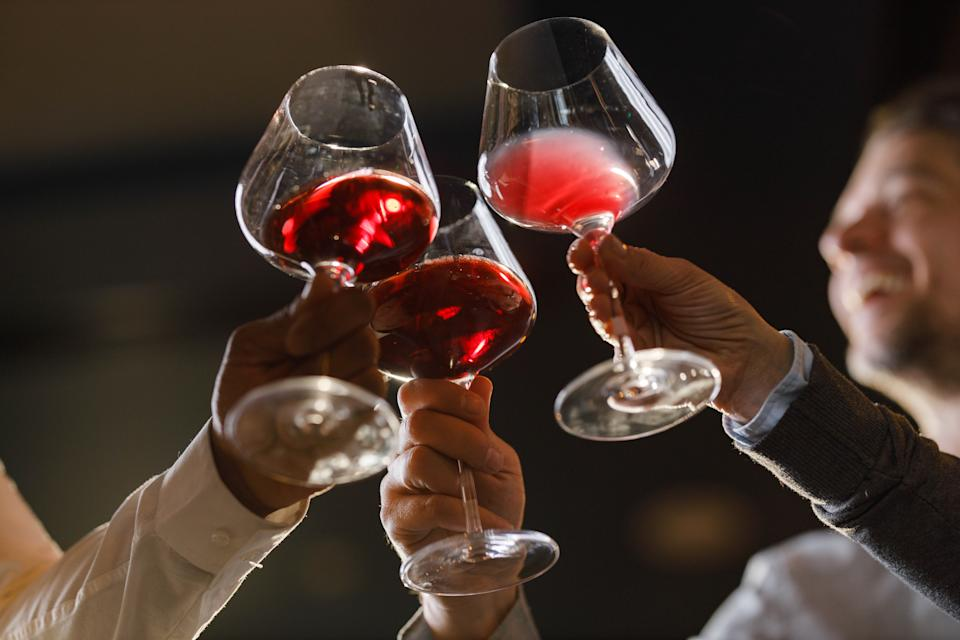 Close up of unrecognizable friends toasting wit red wine.