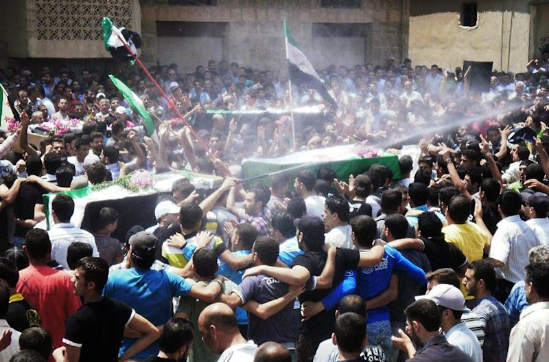 This citizen journalism image provided by Shaam News Network SNN, purports to show an anti-Syrian regime man, center, spraying water over mourners to cool them from the heat as they carry the coffins of Syrian citizens who were killed by the Syrian forces shelling during heir funeral procession, in Daraa, southern Syria, Tuesday June 26, 2012. Syria's elite Republican Guard forces clashed with rebels just outside Damascus Tuesday in some of the most intense fighting involving the special forces guarding the capital since an uprising against President Bashar Assad's regime began last year, activists said. (AP Photo/Shaam News Network, SNN)THE ASSOCIATED PRESS IS UNABLE TO INDEPENDENTLY VERIFY THE AUTHENTICITY, CONTENT, LOCATION OR DATE OF THIS HANDOUT PHOTO