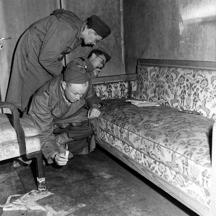 """With only candles to light their way, war correspondents examine a couch stained with blood (see dark patch on the arm of the sofa) located inside Hitler's bunker, 1945. (William Vandivert—Time & Life Pictures/Getty Images) <br> <br> <a href=""""http://life.time.com/history/inside-hitlers-bunker-rare-and-unpublished-photos/#1"""" rel=""""nofollow noopener"""" target=""""_blank"""" data-ylk=""""slk:Click here"""" class=""""link rapid-noclick-resp"""">Click here</a> to see the complete collection of pictures and read the full story at LIFE.com"""