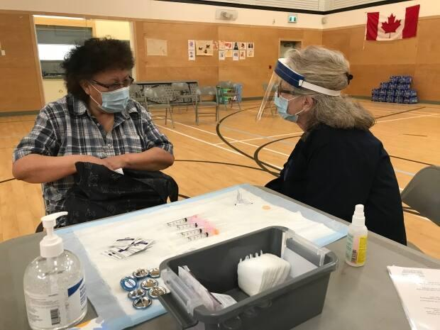 Sheila Laity, right, talks to a patient before administering the second dose of the Moderna vaccine in Nahanni Butte, N.W.T.