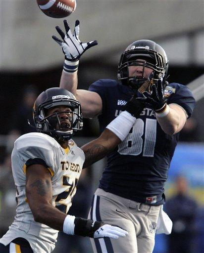 Utah State's Kellen Bartlett (81) makes a reception against Toledo's T.J. Franklin (23) during the first half of an NCAA college football game on Saturday, Dec. 15, 2012, in Boise, Idaho. (AP Photo/Matt Cilley)