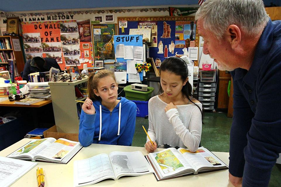 <p>Two seventh graders get some assistance from their teacher during a class on ancient civilizations.</p>