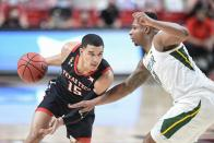 Texas Tech's Kevin McCuller (15) attempts to drive the ball around Baylor's Mark Vital (11) during the first half of an NCAA college basketball game in Lubbock, Texas, Saturday, Jan. 16, 2021. (AP Photo/Justin Rex)