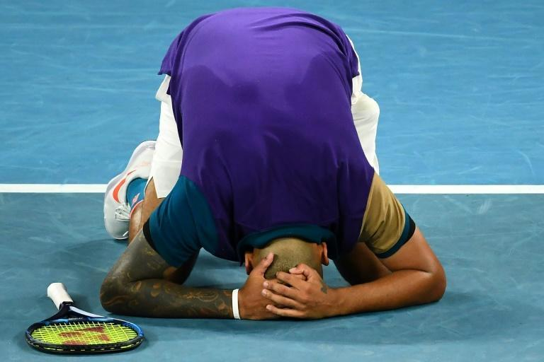 Nick Kyrgios drops down in disbelief after securing match point in a five-set thriller against Ugo Humbert