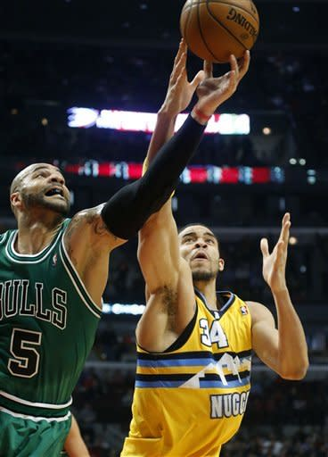 Chicago Bulls forward Carlos Boozer (5) battles Denver Nuggets center JaVale McGee for a loose ball during the first half of an NBA basketball game, Monday, March 18, 2013, in Chicago. (AP Photo/Charles Rex Arbogast)