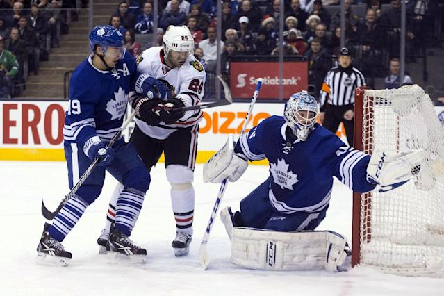 Toronto Maple Leafs goaltender Jonathan Bernier, right, stretches to make a save as Chicago Blackhawks' Michal Handzus, center, and Leafs' Joffrey Lupul skate near during the first period of an NHL hockey game in Toronto on Saturday, Dec. 14, 2013. (AP Photo/The Canadian Press, Chris Young)
