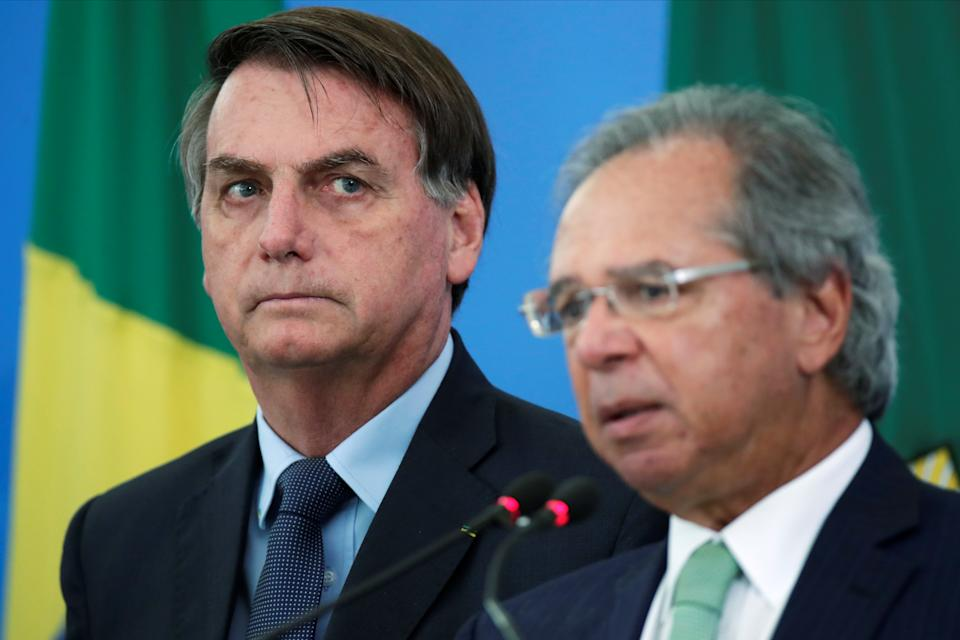 Brazil's President Jair Bolsonaro listens Brazil's Economy Minister Paulo Guedes during a media statement announcing economic measures, amid coronavirus disease (COVID-19) outbreak, in Brasilia, Brazil, April 1, 2020. REUTERS/Ueslei Marcelino