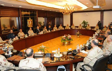 Egypt's interim President Adly Mansour (L, in suit and tie) meets with Egypt's army chief Field Marshal Abdel Fattah al-Sisi (seated next to Mansour) and military leaders, in Cairo March 26, 2014. REUTERS/Egyptian Ministry of Defence/Handout