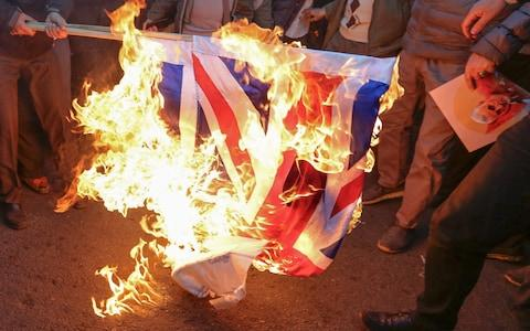 <span>Iranian demonstrators set alight a Union Jack in front of the British embassy in Iran's capital Tehran</span>