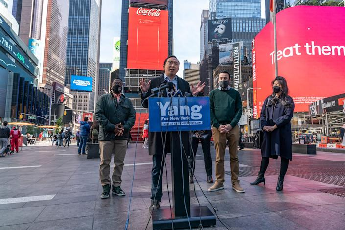Yang stands at a podium in Times Square.
