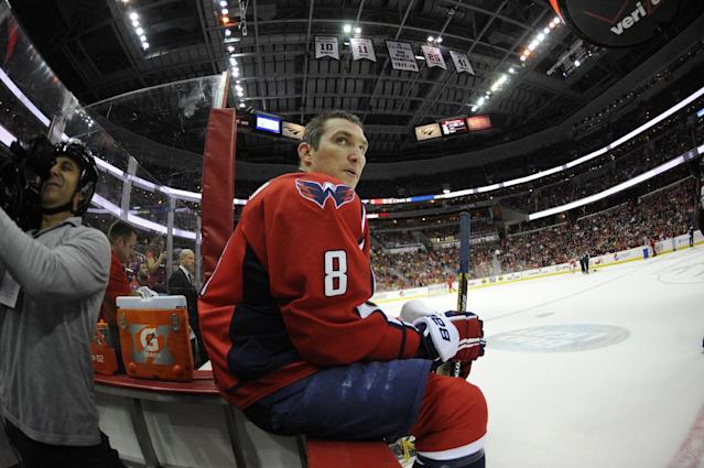 In this photo taken with a fisheye lens, Washington Capitals right wing Alex Ovechkin (8), of Russia, looks on during a break in the action in the first period of an NHL hockey game against the Boston Bruins, Saturday, March 29, 2014, in Washington. (AP Photo/Nick Wass)