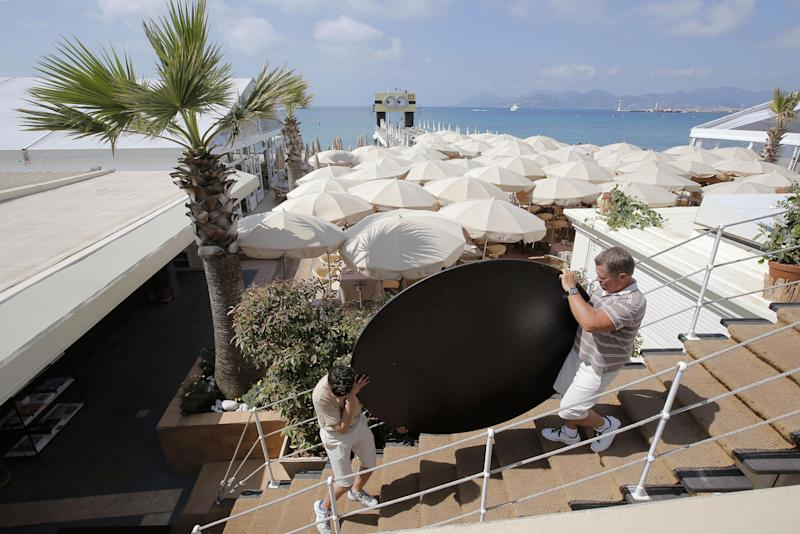 Workers make final preparations at a beach ahead of the 66th international film festival, in Cannes, southern France, Tuesday, May 14, 2013. (AP Photo/Lionel Cironneau)