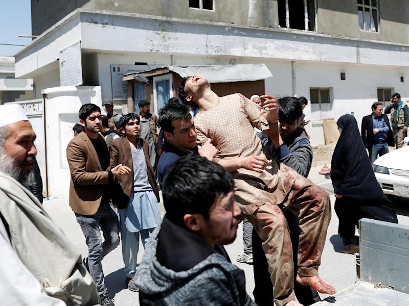 Relatives of the victims carry an injured man outside a hospital after a suicide attack in Kabul: Reuters