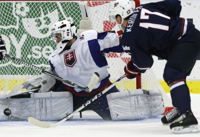 Slovakia's goalie Richard Sabol makes a save on Nicolas Kerdiles (R) of the U.S. during the second period of their IIHF World Junior Championship ice hockey game in Malmo, Sweden, December 28, 2013. REUTERS/Alexander Demianchuk (SWEDEN - Tags: SPORT ICE HOCKEY)