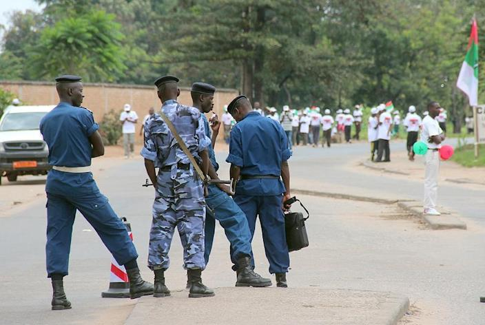 Burundi's security forces stand in a street in Bujumbura as crowds of members of the ruling party on April 25, 2015 walk past (AFP Photo/Landry Nshimiye)