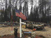 FILE - In this Dec. 5, 2018, file photo, a flag flies amid the remains of Jerry and Joyce McLean's home destroyed by the Camp Fire in Paradise Calif. The McLean's home is one of nearly 9,000 Paradise homes destroyed in the deadliest and most destructive wildfire in California history. (AP Photo/Don Thompson, File)