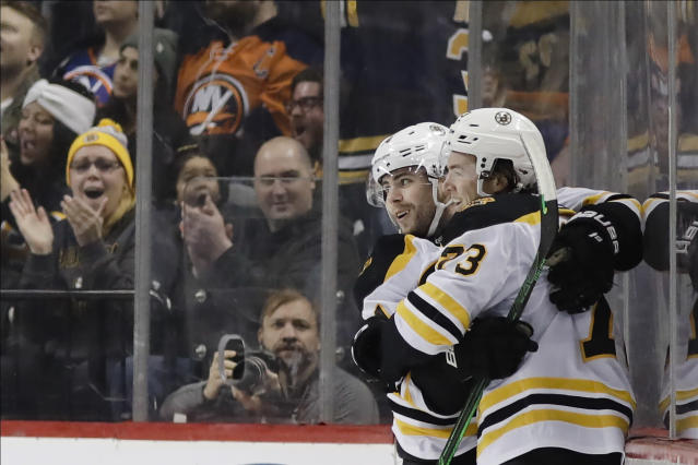 Boston Bruins' Jake DeBrusk, left, celebrates with teammate Charlie McAvoy (73) after scoring a goal during the second period of an NHL hockey game against the New York Islanders, Saturday, Jan. 11, 2020, in New York. (AP Photo/Frank Franklin II)
