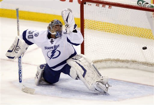 Tampa Bay Lightning goalie Dwayne Roloson looks over his shoulder as he allows a goal from Ottawa Senators center Kyle Turris during the second period of an NHL hockey game in Ottawa, Ontario, on Thursday, Jan. 5, 2012. (AP Photo/The Canadian Press, Adrian Wyld)