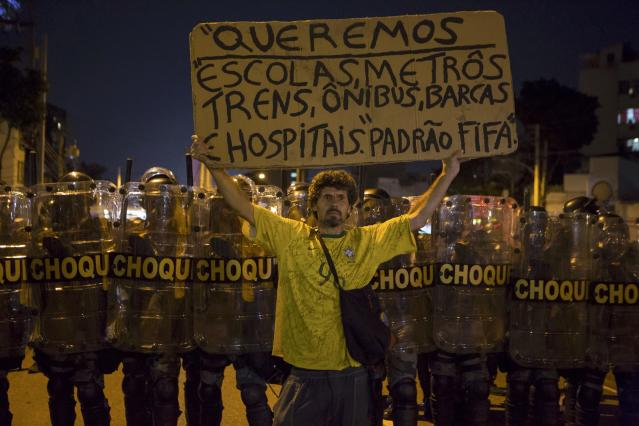 "A protester stands in front of riot police during a demonstration against the public spending for the 2014 World Cup, in Rio de Janeiro June 15, 2014. The sign reads, ""We want schools, subways, trains, buses, boats, hospitals of FIFA standard."" Police blocked the streets to keep demonstrators from reaching Maracana soccer stadium as Argentina played Bosnia and Herzegovina for Group F. REUTERS/Stringer/Brazil/Marco Bello (BRAZIL - Tags: SPORT SOCCER WORLD CUP CIVIL UNREST POLITICS)"