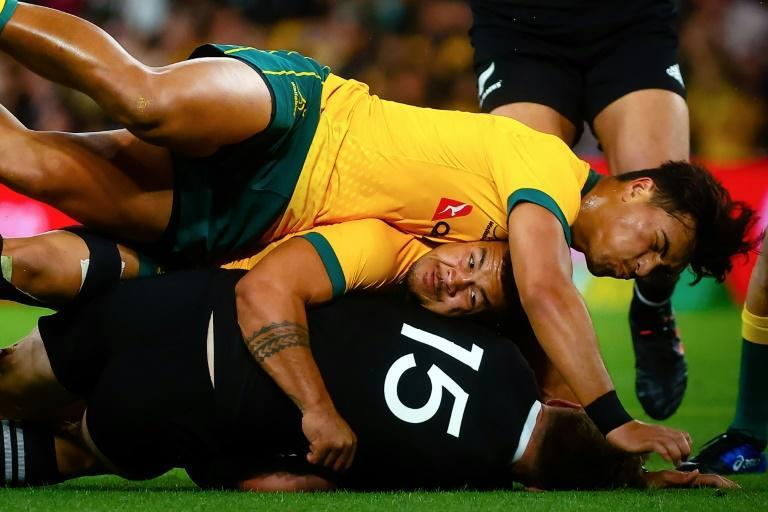 Australia's Jordan Petaia (top) tackles New Zealand's Jordie Barrett during the Tri Nations and Bledisloe Cup match in Brisbane