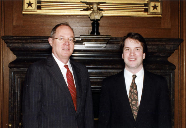 In this image provided by the Department of Justice, Brett Kavanaugh stands with Supreme Court Justice Anthony Kennedy. Kavanaugh has been a conservative team player, and the Supreme Court nominee has stepped up to make a play at key moments in politics, government and the law dating to the Bill Clinton era. (DoJ via AP)