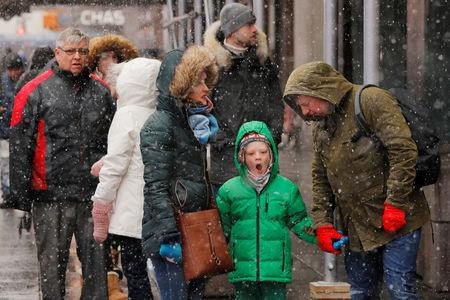 A young boy yawns while walking through the Times Square neighborhood during a snowfall in New York, U.S., February 12, 2019.  REUTERS/Lucas Jackson