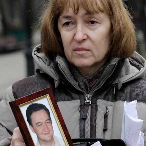 Nataliya Magnitskaya, the mother of Sergei Magnitsky, holds a photo of her son following his death in a Russian jail in 2009 - Credit: Alexander Zemlianichenko/AP