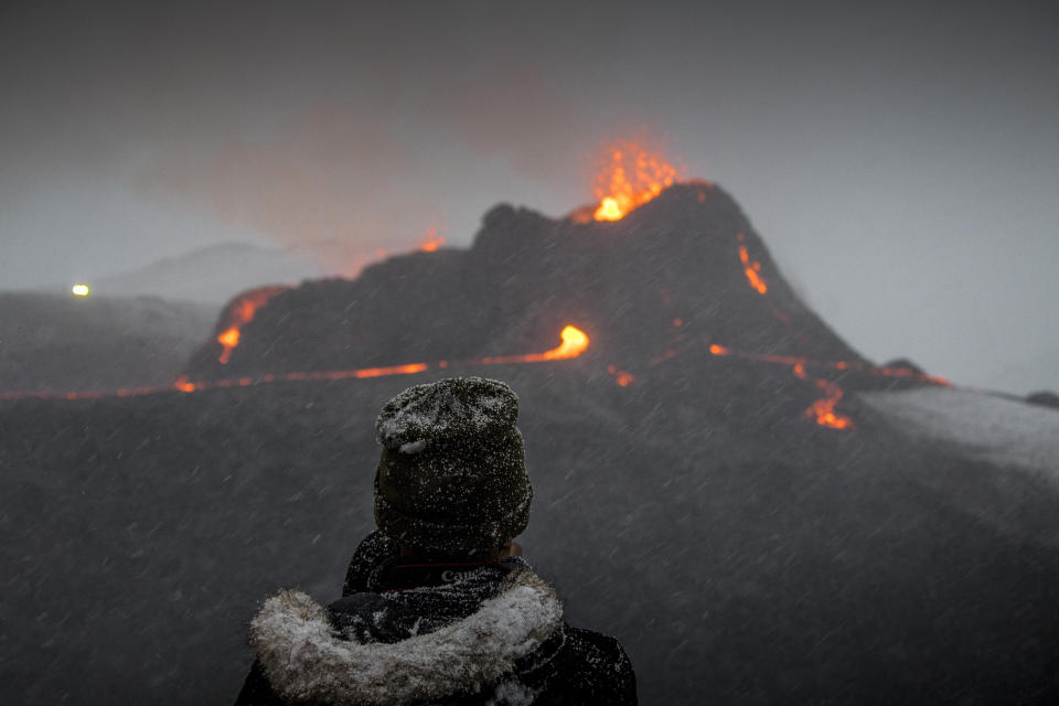 A person watches as lava flows from an eruption of a volcano on the Reykjanes Peninsula in southwestern Iceland on Wednesday, March 24, 2021. The eruption in Geldingadalur, near Iceland's capital Reykjavik, is not seen as a threat to nearby towns and the slow flows mean people can get close to the scene without too much harm. (AP Photo/Marco Di Marco)