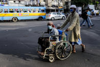 A man pushes a disabled man on wheelchair, both wearing face masks to prevent spreading coronavirus in Kolkata, India, Monday, Oct. 5, 2020. India, the second worst-affected nation in the world after the United States, is witnessing a sustained decline in new coronavirus infections and active virus cases have remained below the million mark for 14 consecutive days. (AP Photo/Bikas Das)