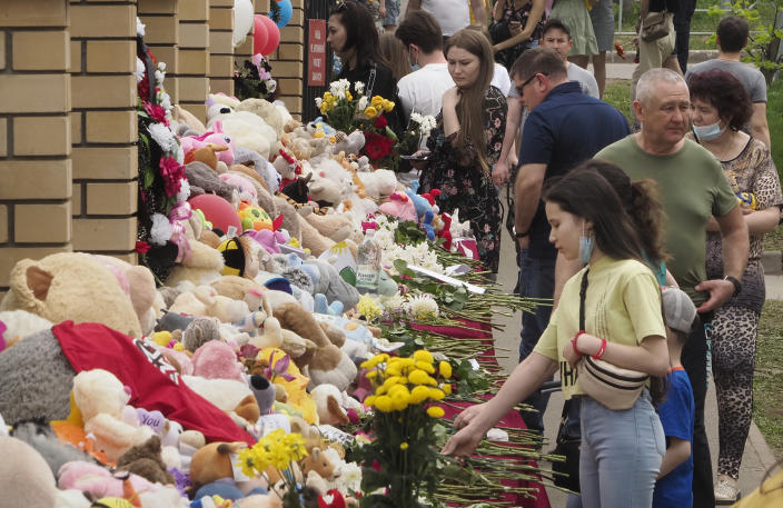 People lay flowers and toys near a school after a shooting on Tuesday in Kazan, Russia, Thursday, May 13, 2021. Russian officials say a gunman attacked a school in the city of Kazan and Russian officials say several people have been killed. Officials said the dead in Tuesday's shooting include students, a teacher and a school worker. Authorities also say over 20 others have been hospitalised with wounds. (AP Photo/Dmitri Lovetsky)
