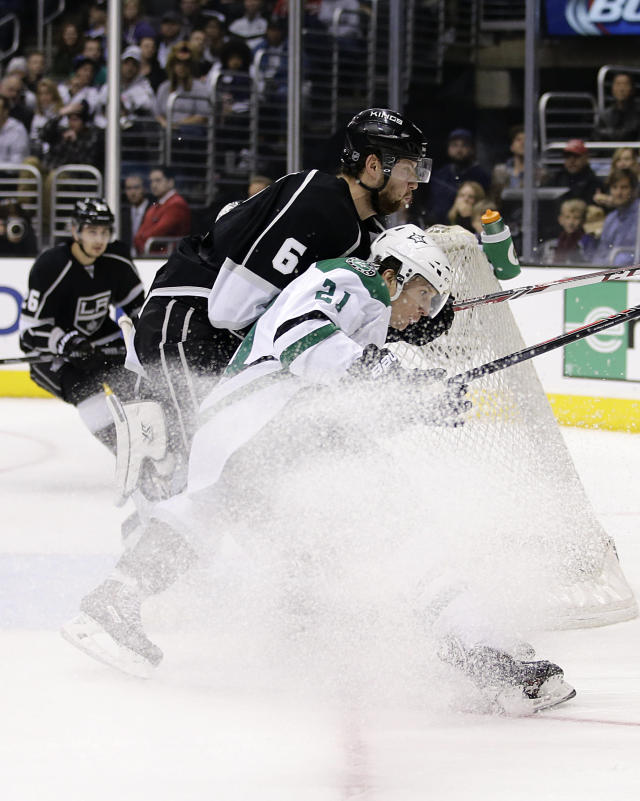 Los Angeles Kings' Jake Muzzin, left, and Dallas Stars' Antoine Roussel, of France, collide during the first period of an NHL hockey game on Monday, Dec. 23, 2013, in Los Angeles. (AP Photo/Jae C. Hong)