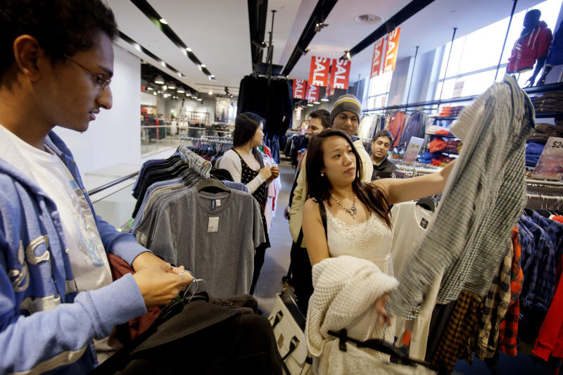 In this Wednesday, Dec. 12, 2012, photo, Lana Nguyen, right, holds up a shirt while helping friend Chris Ghiathi, left, shop in an H&M store, in Atlanta. U. S. consumers increased their spending in December at a slower pace, while their income grew by the largest amount in eight years. Income surged because companies rushed to pay dividends before income taxes increased on high-earners. (AP Photo/David Goldman)