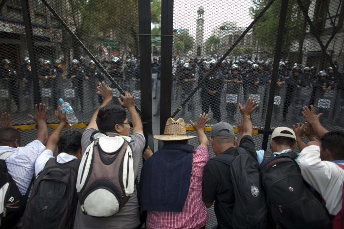 Public school teachers push to open a fence that blocks a street near Mexico's Interior Ministry as Federal Police officers watch during a demonstration in Mexico City, Thursday, April 4, 2013. Radical Mexican public school teachers are holding marches and blocking roads to battle a newly enacted education reform that would weaken union powers. (AP Photo/Alexandre Meneghini)