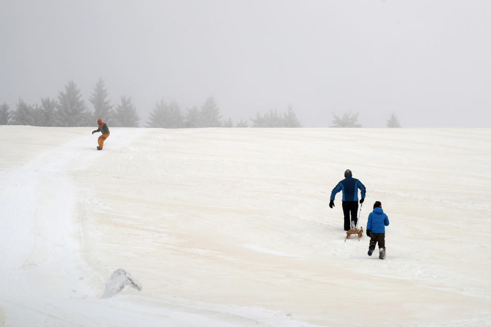 People enjoy the day as Sahara sand colours the snow near Altenberg, Germany, Sunday, Feb. 7, 2021. (AP Photo/Matthias Schrader)