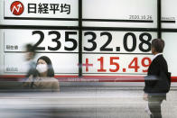 Pedestrian stand near an electronic stock board showing Japan's Nikkei 225 index at a securities firm in Tokyo Monday, Oct. 26, 2020. Asian shares were little changed in muted trading Monday amid widespread uncertainty over what the U.S. presidential election will portend for markets and economic policy.(AP Photo/Eugene Hoshiko)
