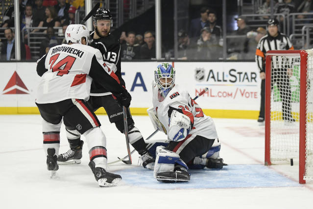 Los Angeles Kings left wing Kyle Clifford, center, scores on Ottawa Senators goaltender Anders Nilsson, right, and defenseman Mark Borowiecki during the second period of an NHL hockey game Thursday, Jan. 10, 2019, in Los Angeles. (AP Photo/Mark J. Terrill)