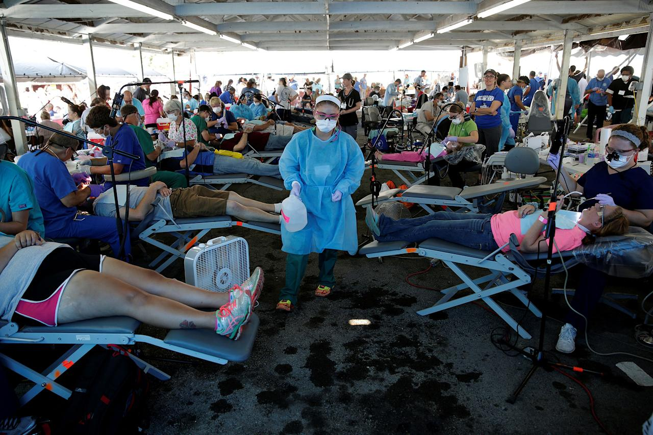 <p>A volunteer walks past people receiving dental care at the Remote Area Medical Clinic in Wise, Va., July 21, 2017. (Photo: Joshua Roberts/Reuters) </p>