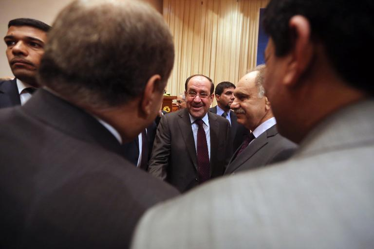 Iraqi Prime Minister Nuri al-Maliki (C) talks with Kurdish MPs as he arrives for the first session of the new parliament on July 1, 2014 in the capital Baghdad