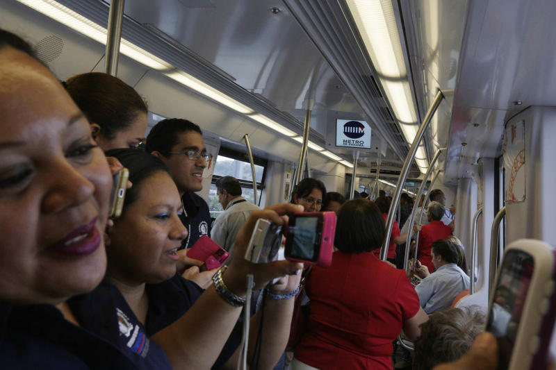 "In this Wednesday, April 2, 2014 photo, government employees and their guests take photos as they ride on a subway while participating in an invitation to test the wagons of the new ""Metro de Panama,"" or Panama Metro in Panama City. Central America's first underground metro will surely alleviate the booming capital's dreadful traffic. But critics say the $2 billion spent on the 14-kilometer rail project, which was marred by cost overruns, would've been better used building a higher-capacity, surface transport network. They also are blasting the timing of the over-the-top inauguration set for Saturday, April 5, which they say is a political stunt by president Ricardo Martinelli to drum up support for his preferred successor. (AP Photo/Arnulfo Franco)"