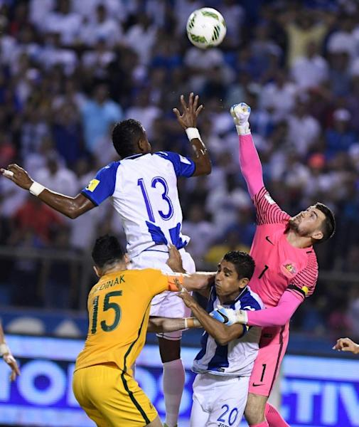 Australia's goalkeeper Mathew Ryan (R) jumps for the ball during their FIFA 2018 World Cup qualifying play-off first leg match against Honduras, in San Pedro Sula, Honduras, on November 10, 2017