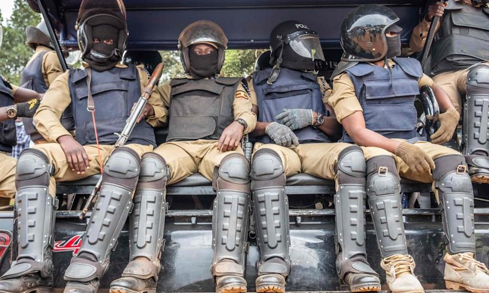 Ugandan police officers sit on a truck at a polling station in Magere on Thursday.