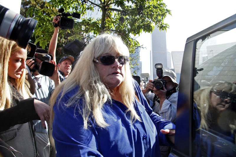 In this Wednesday, Aug. 14, 2013 file photo, Debbie Rowe, Michael Jackson's former wife and mother of two of his children, leaves Los Angeles County Superior Court after testifying in the negligence lawsuit filed by Jackson's mother, Katherine Jackson, against AEG Live, in Los Angeles. Rowe told a Los Angeles jury on Thursday, Aug. 15, 2013, that injuries and medical conditions left the singer feeling disfigured and forced him to wear wigs and de-pigment his skin. These difficult treatments she said were made harder by Jackson's superstar status. (AP Photo/Nick Ut, File)