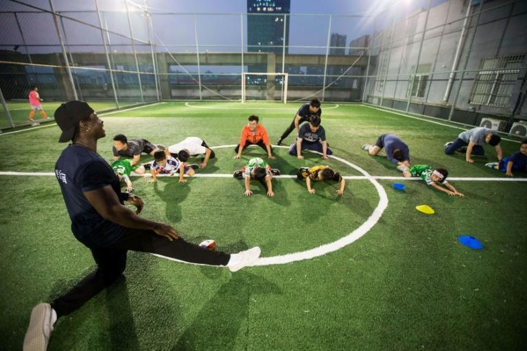 Coach Paul Rene takes the children through stretching exercises with their parents during training at Hangzhou Clovers American Football Club